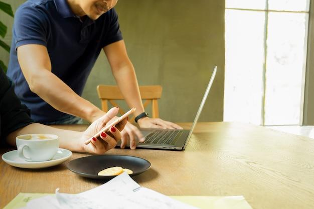 Lavoro della squadra di affari facendo uso del telefono cellulare e del computer portatile che lavorano con i documenti