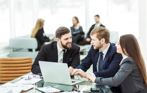 Squadra di affari che lavora al laptop e che fa il rapporto finanziario corrente seduto alla tua scrivania in ufficio.