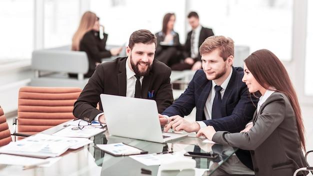 Squadra di affari che lavora al computer portatile con i record finanziari nell'ufficio moderno