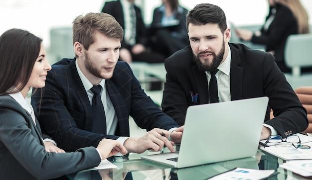 Squadra di affari che lavora al computer portatile con i record finanziari nell'ufficio moderno.