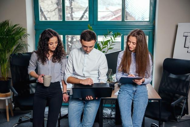 Squadra di affari di giovani architetti o designer che creano nuovo progetto mentre lavorano nell'ufficio moderno ed elegante con una grande finestra.