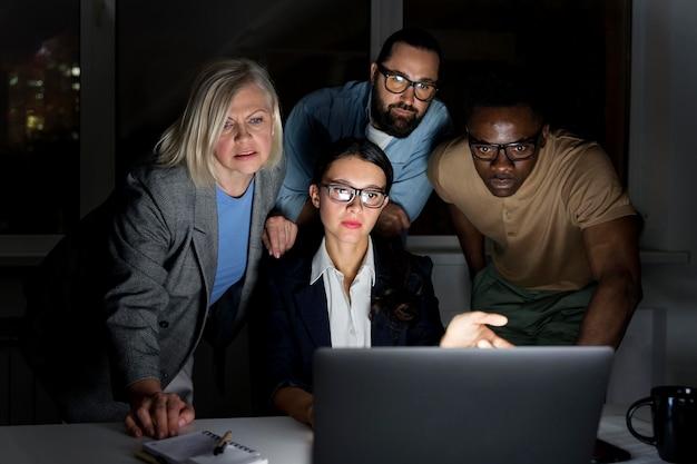 Compagni di squadra di lavoro che lavorano fino a tardi in ufficio