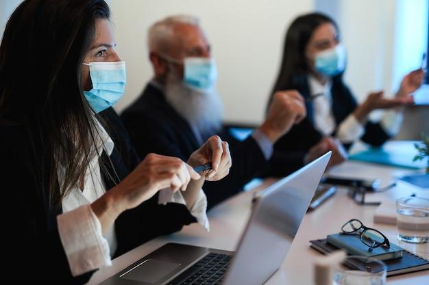 Lavoro di squadra aziendale che fa riunioni all'interno dell'ufficio bancario indossando una maschera di sicurezza durante l'epidemia di coronavirus