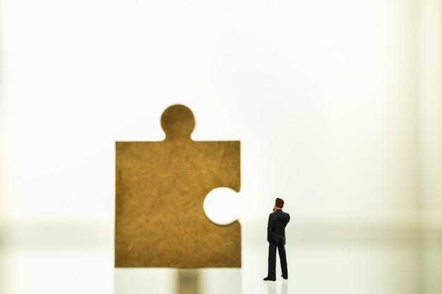 Concetto di affari, lavoro di squadra, pianificazione e lavoro. chiuda su della figura miniatura miniatura dell'uomo d'affari che sta e che guarda al pezzo di puzzle di legno con lo spazio della copia.