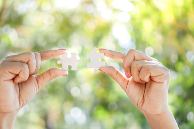 Lavoro di squadra di affari, concetto di unità con il puzzle della tenuta della mano