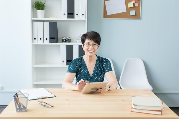 Concetto di affari, tecnologia e persone - donna di mezza età si siede al tavolo e utilizza un tablet.