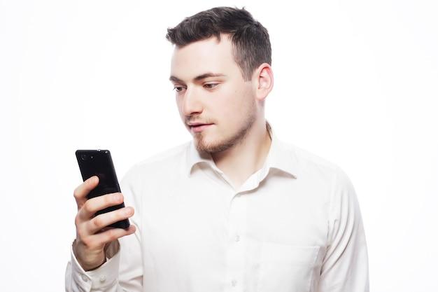 Concetto di affari, tecnologia e persone - un bell'uomo d'affari felice che legge un sms su smartphone su sfondo bianco