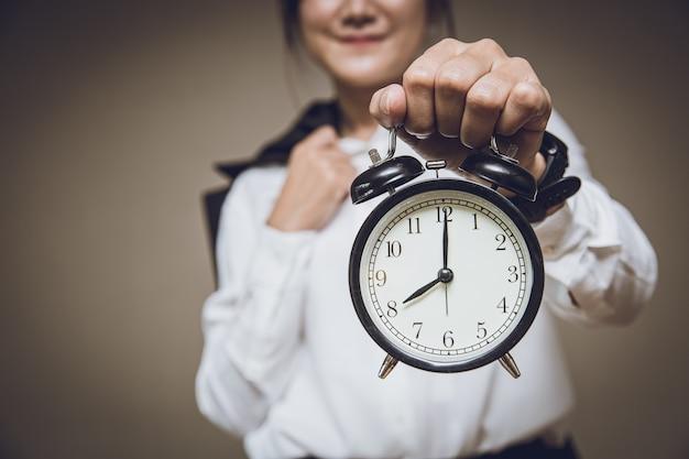 L'orologio dell'orario di lavoro o l'orario di lavoro mattutino ricordano il concetto di avviso di avviso, le persone che tengono la sveglia a campana retrò.