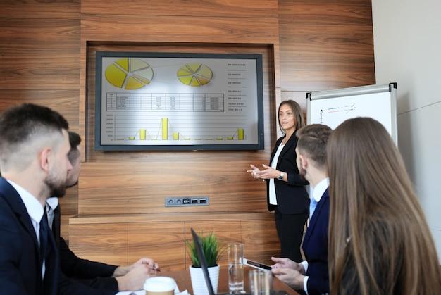 Formazione aziendale in ufficio, donna d'affari che presenta numeri finanziari di successo sullo schermo della tv al plasma nella sala riunioni