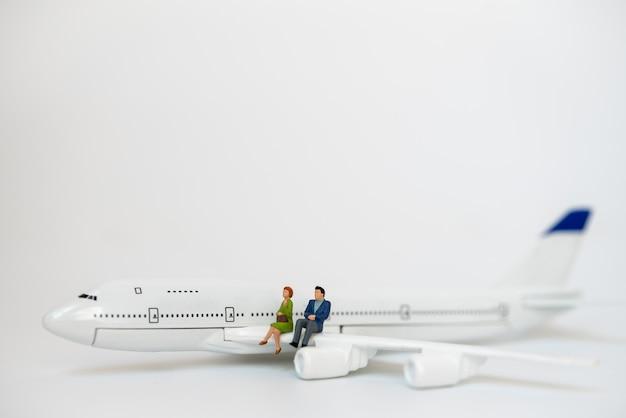 Business e concetto di viaggio. imprenditore e imprenditrice figura in miniatura persone sedute sull'ala del modello di mini aeroplano