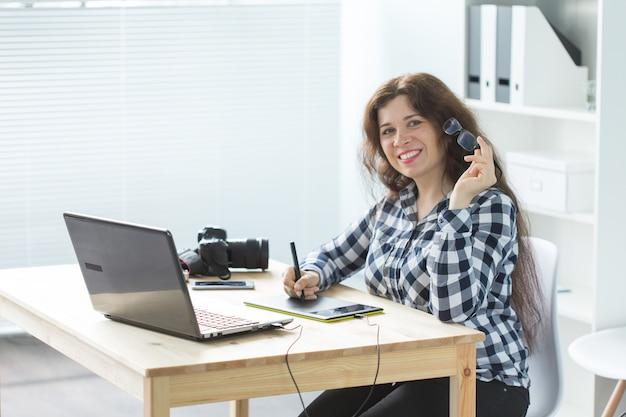 Concetto di affari, web design e persone - la donna usa la tavoletta grafica nel lavorare al computer portatile e nel sorridere