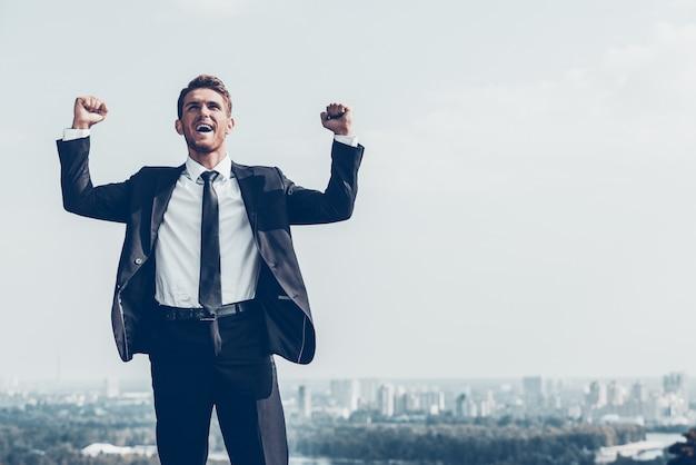 Vincitore di affari. felice giovane in abiti da cerimonia che tiene le braccia alzate ed esprime positività mentre si trova all'aperto con il paesaggio urbano sullo sfondo