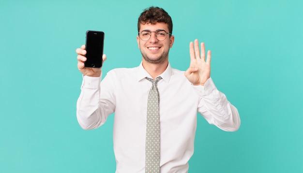 Affari con uno smartphone sorridente e amichevole, che mostra il numero quattro o il quarto con la mano in avanti, conto alla rovescia