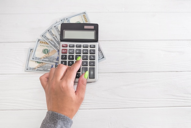 Ragioniere o banchiere della donna di affari che fa i calcoli risparmio, finanziamento aziendale contabilità bancaria e concetto di economia. immagine delle mani con soldi e calcolatrice sul tavolo con spazio di copia