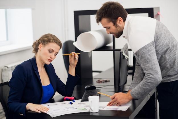 Una donna d'affari che analizza il documento che il suo dipendente le ha appena presentato