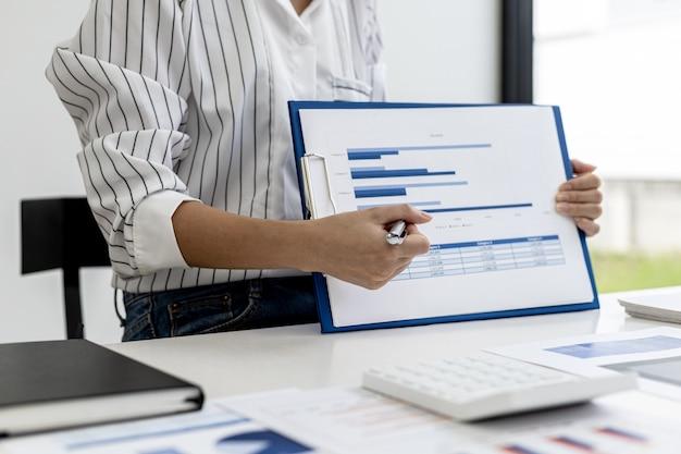 La donna d'affari sta esaminando i documenti finanziari dell'azienda per analizzare i problemi e trovare soluzioni prima di portare le informazioni a un incontro con un partner. concetto finanziario.