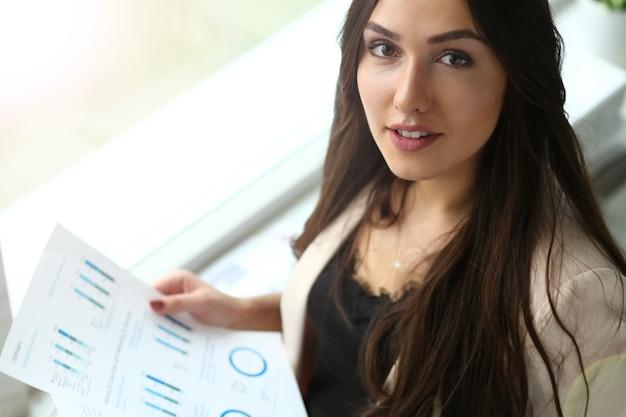 Donna d'affari in abito beige analizzando i documenti