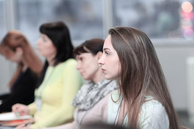 Donna d'affari su sfondo sfocato dei colleghi nella sala conferenze.