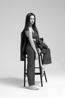 Una donna d'affari in giacca e cravatta si siede su un seggiolone su uno sfondo grigio.