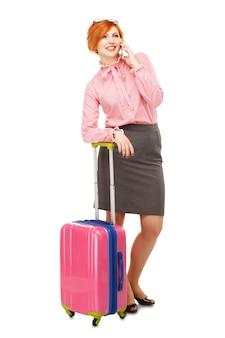 Donna d'affari in viaggio d'affari con una valigia su ruote parlando mobile e sorridente