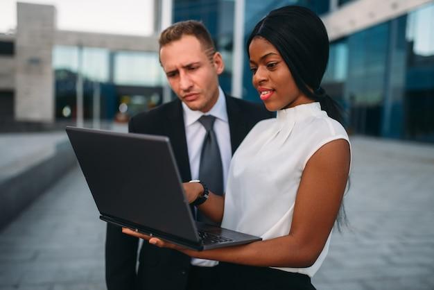 La donna e l'uomo d'affari di affari osserva sul computer portatile