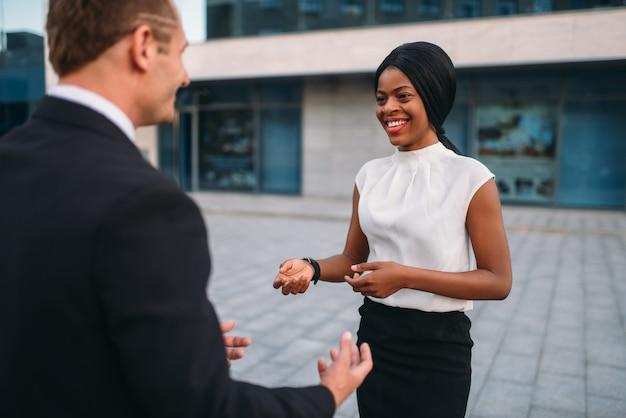 Donna d'affari e uomo d'affari, incontro all'aperto dei partner, negoziati di partenariato. uomini d'affari di successo