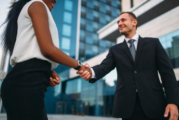 Donna d'affari e uomo d'affari si stringono la mano, incontro all'aperto dei partner, moderno edificio per uffici
