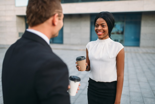 Donna d'affari e uomo d'affari con tazze di caffè, riunione all'aperto dei partner, moderno edificio per uffici