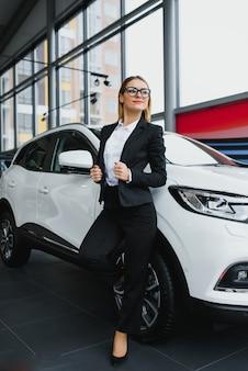 La donna di affari acquista un'auto presso una concessionaria di automobili