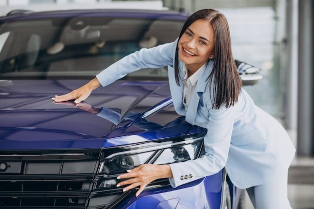 Donna d'affari che sceglie una nuova auto in uno showroom di auto