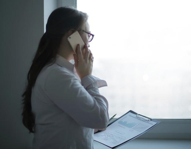 Donna d'affari discutendo documenti finanziari su smartphone.