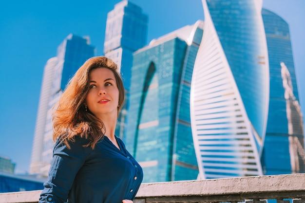 Donna d'affari in un vestito con grattacieli di vetro