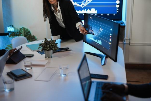 Donna d'affari che spiega le strategie di trading all'interno della sala riunioni della banca - focus sulla mano che punta sullo schermo