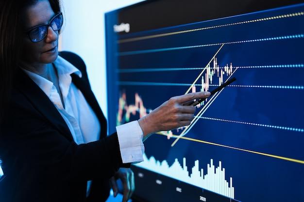 Donna d'affari che spiega le strategie di trading all'interno della sala riunioni della banca