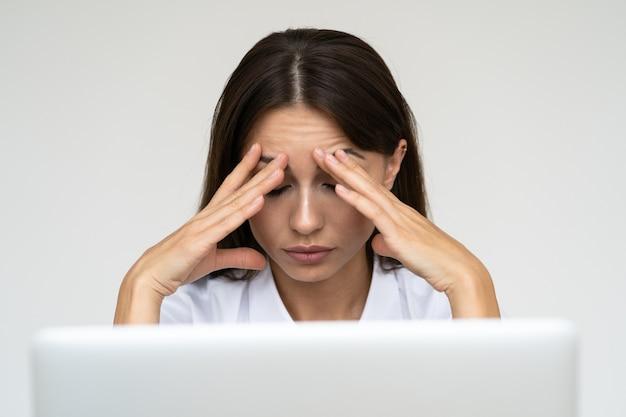 Donna d'affari sensazione di mal di testa dal lavoro sul computer portatile