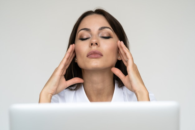 Donna d'affari sensazione di mal di testa davanti al computer portatile in ufficio a casa