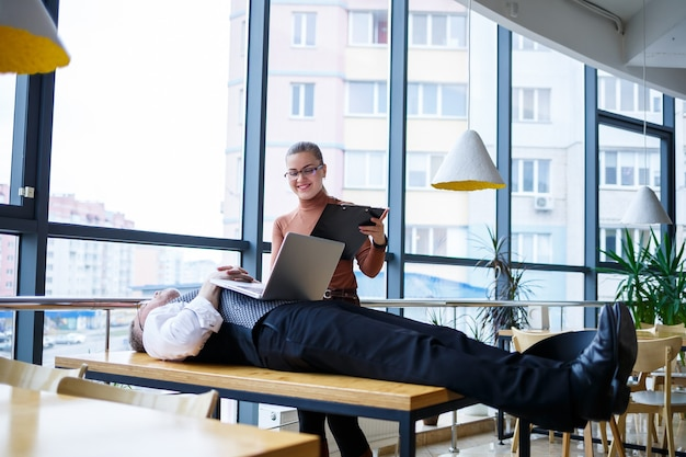 Una ragazza della donna di affari sta levandosi in piedi e sta leggendo un rapporto; un capo stanco è sdraiato su un tavolo a un tavolo di legno. l'uomo d'affari sta riposando e lavora come subordinati