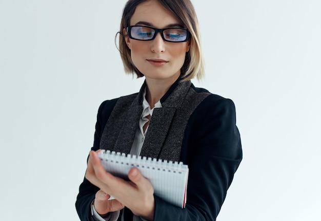 Donna d'affari con gli occhiali con ufficio documenti blocco note