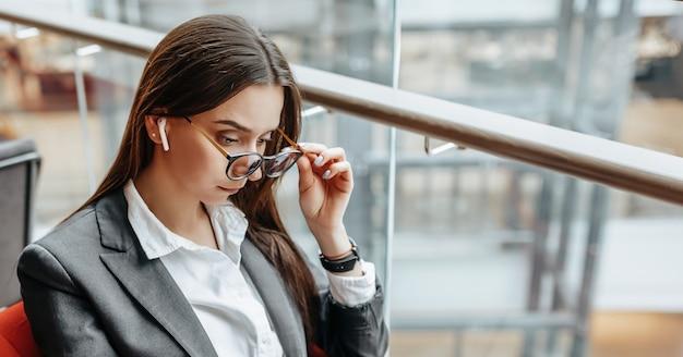Donna d'affari in bicchieri sul posto di lavoro utilizza il telefono e si siede al tavolo