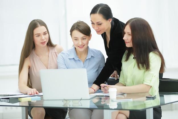 Donna d'affari e gruppo di giovani dipendenti che usano il laptop per lavorare