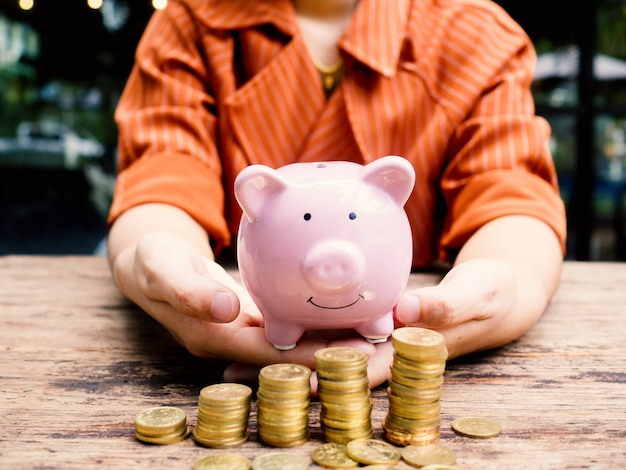 La mano della donna di affari porta il porcellino salvadanaio rosa con il grafico di crescita del mucchio delle monete d'oro, il risparmio di denaro per il futuro piano di investimento e il concetto di fondo pensione.