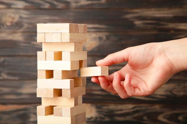 Mano di donna d'affari raccogliere e mettere l'ultimo blocco pezzo del puzzle di legno. blocco di legno su sfondo marrone