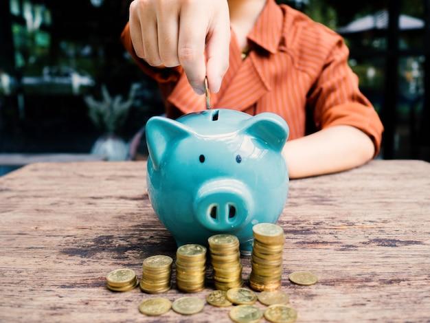 Mano della donna di affari che mette moneta nel salvadanaio blu con il grafico di crescita del mucchio delle monete d'oro, risparmio di denaro per il futuro piano di investimento e concetto di fondo pensione.