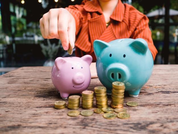 Mano della donna di affari che mette moneta nel salvadanaio con il grafico di crescita del mucchio delle monete d'oro, risparmio di denaro per il futuro piano di investimento e concetto di fondo pensione.