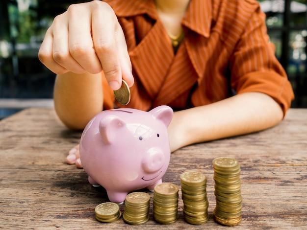 Mano della donna di affari che mette moneta nel salvadanaio rosa con il grafico di crescita del mucchio delle monete d'oro, risparmio di denaro per il piano di investimento futuro e il concetto di fondo pensione.