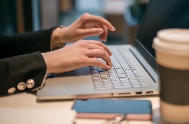 Donna d'affari, lavoro a mano su un notebook, con caffè e smartphone in primo piano