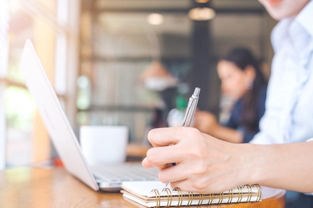 Mano della donna di affari che lavora in un computer e che scrive con una penna ad un blocco note nell'ufficio