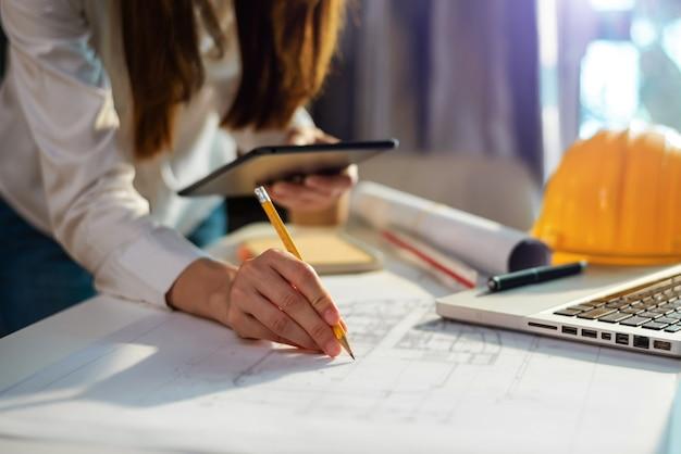 Donna d'affari che lavora a mano e laptop con acceso su un progetto architettonico in cantiere alla scrivania dell'ufficio