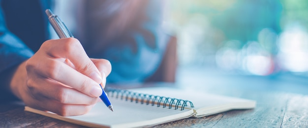 Mano della donna di affari che scrive su un blocco note con una penna nell'ufficio.