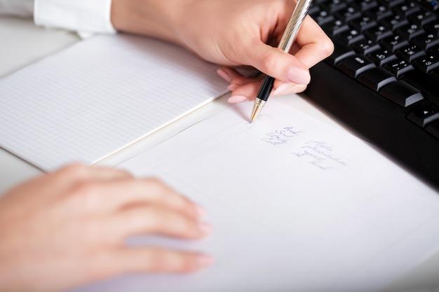 Scrittura della mano della donna di affari su carta. mano e blocco note da vicino